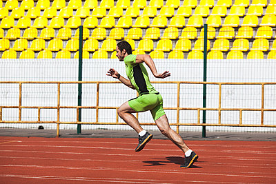 Full length side view of sporty young man running on race track in stadium - p301m1102028f by Vasily Pindyurin