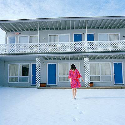Woman in Pink Dress Walking through Snow at Motel, Rear View - p694m1175545 by Nancy Grace Horton