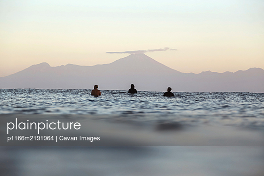 Surfers on surfboard on the sea waiting for a wave, Volcano Rinjani - p1166m2191964 by Cavan Images
