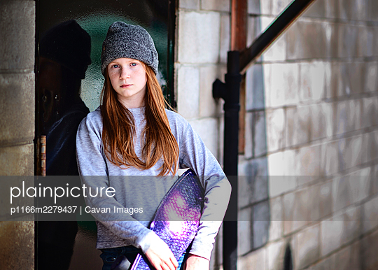 Tween girl with red hair and hat posing with skateboard. - p1166m2279437 by Cavan Images