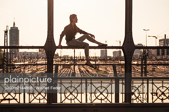Young woman sitting on Hacker bridge at sunset, Munich, Germany - p300m2144868 by Wilfried Feder
