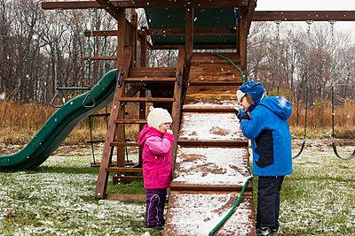 Siblings eating food while standing in backyard during winter - p1166m1203781 by Cavan Images
