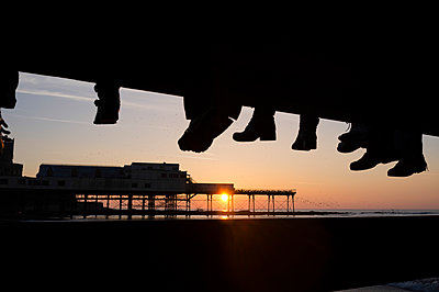 The feet of a group of friends watching a murmuration of starlings roosting on the cast iron legs of Aberystwyth pier at sunset  - p1403m1482610 by Photofusion