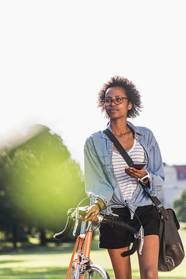 Young woman with cell phone pushing bicycle in park - p300m2024154 by Uwe Umstätter