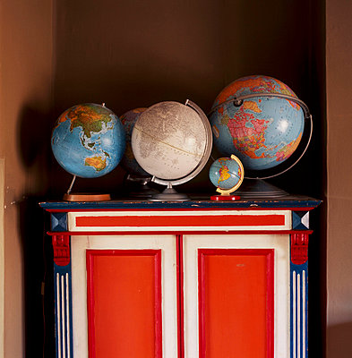 Collection of globes on a painted unit - p349m695218 by Emma Lee