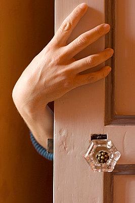 Woman hiding behind a door - p8700037 by Gilles Rigoulet