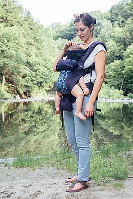Portrait of young woman carrying baby daughter in sling on riverbank - p924m1094700f by Ashley Corbin-Teich