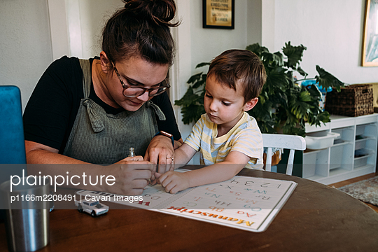 Mom and young son painting finger nails at kitchen table - p1166m2208491 by Cavan Images