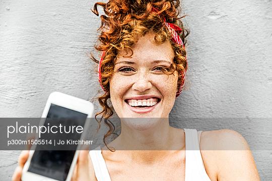 plainpicture | Photo library for authentic images - plainpicture p300m1505514 - Happy redheaded woman showi... - plainpicture/Westend61/Jo Kirchherr