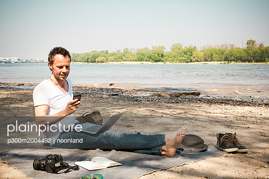 Man sitting on blanket at a river using laptop and cell phone - p300m2004492 von noonland