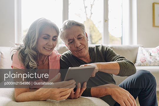 Happy senior couple relaxing on couch at home using tablet - p300m2154986 by Gustafsson