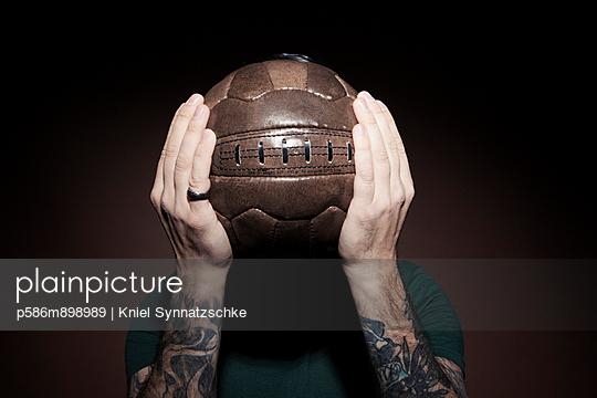 Mann versteckt sein Gesicht hinter einem Fußball - p586m898989 von Kniel Synnatzschke