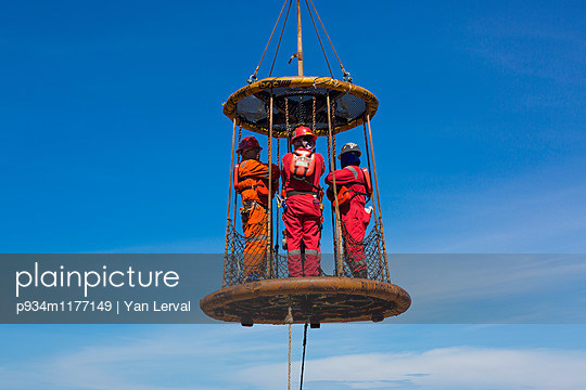 Workers lifted in a basket on an oil rig offshore of Vung Tau, Vietnam, Southeast Asia - p934m1177149 by Yan Lerval photography