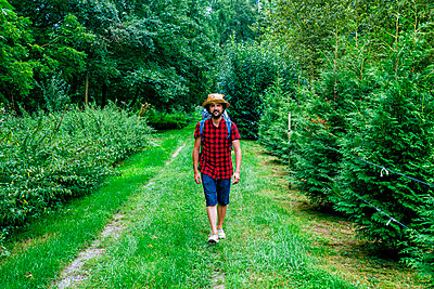 France, Strasbourg, man with travel backpack and straw hat walking on forest path - p300m1535594 by Kiko Jimenez