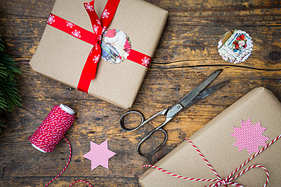 Wrapped Christmas presents and scissors  on dark wood - p300m978034f by Larissa Veronesi