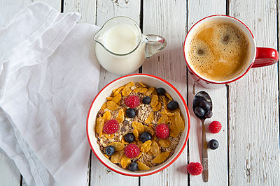 Bowl of granola with fresh fruits, cup of coffee and milk jug on white wood - p300m979009f by Sandra Roesch