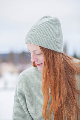Thoughtful young woman with long red hair wearing knit hat and sweater against clear sky - p301m1482458 by Isabella Ståhl