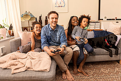 Family playing video game - p312m2051359 by Susanne Kronholm