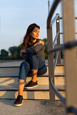 Junge Frau auf Treppenstufe, Portrait - p341m2210457 von Mikesch