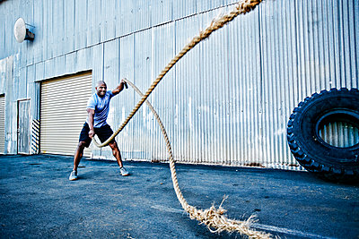 Black man working out with heavy ropes outdoors - p555m1304127 by Peathegee Inc