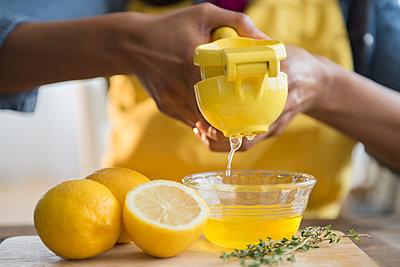 Mixed race woman squeezing lemons - p555m1420238 by JGI/Jamie Grill