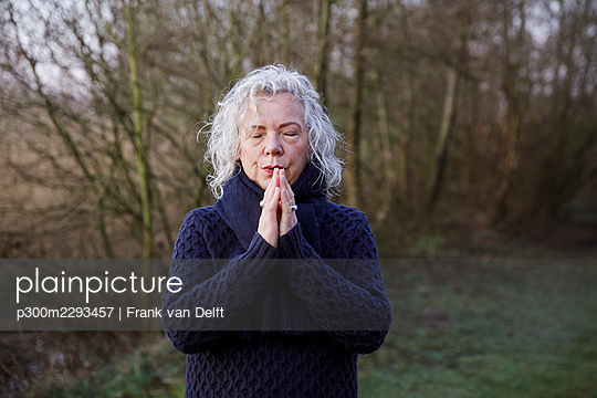 Senior woman with hands clasped standing in front of bare trees - p300m2293457 by Frank van Delft