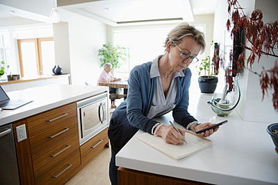 Mature woman with smart phone working from home, writing in notebook in kitchen - p1192m2088384 by Hero Images
