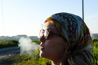 Young woman smoker is exhaling tobacco smoke - p1363m2013496 by Valery Skurydin