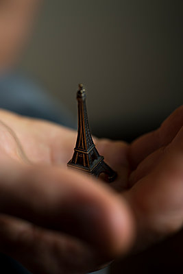 Cupped male hand holding a miniature of the Eiffel tower. - p1433m1586831 by Wolf Kettler