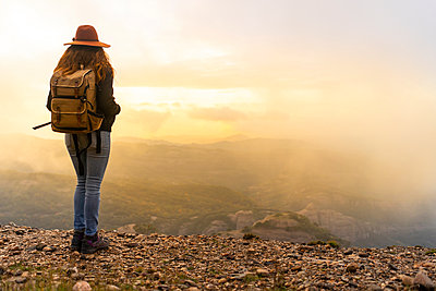 Woman with backback, standing on mountain, looking at view - p300m2078738 von VITTA GALLERY