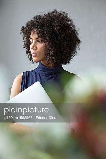 Hübsche Geschäftsfrau mit Afro steht in einem Büro und hält ihren Laptop in der Hand  - p1301m1582963 von Delia Baum