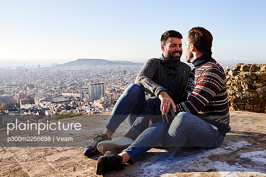 Happy gay couple sitting on observation point during weekend, Bunkers del Carmel, Barcelona, Spain - p300m2256698 by Veam