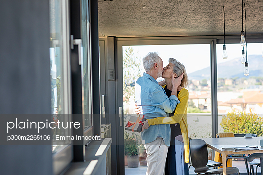 Senior woman with gift box kissing man while standing at home - p300m2265106 by Emma Innocenti