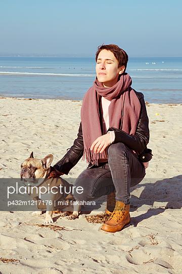 Frau mit Hund am Strand - p432m1217176 von mia takahara