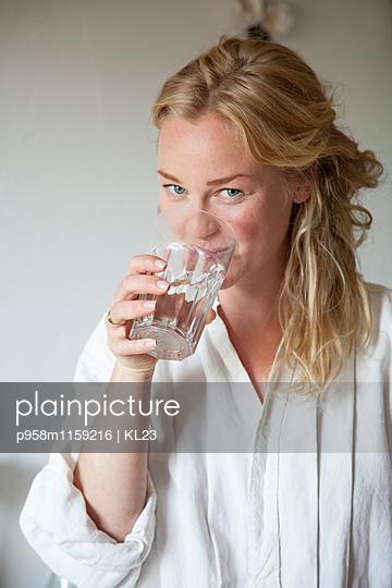 Junge Frau mit Glas Wasser  in der Hand - p958m1159216 von KL23
