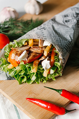 High angle view of wrap sandwich on cutting board - p1166m1543246 by Cavan Social
