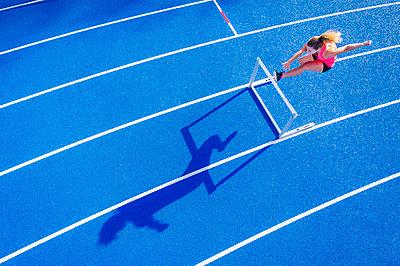 Top view of female runner crossing hurdle on tartan track - p300m2069447 by Stefan Schurr