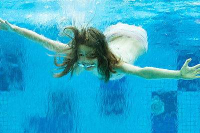 Girl swimming underwater in swimming pool - p623m659071f by Thierry Foulon