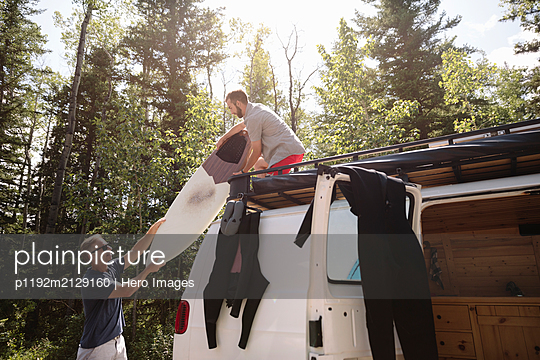 Male surfers unloading surfboard from top of camper van - p1192m2129160 by Hero Images