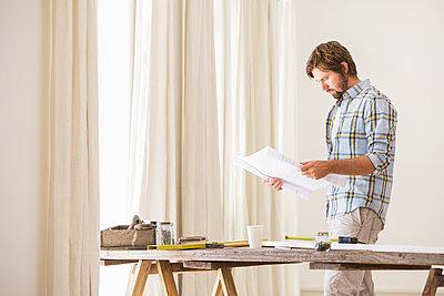 Man looking through documents - p1023m962421f von Martin Barraud