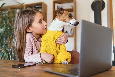 Cute girl looking at dog while sitting with laptop and smart phone at table - p300m2275867 by Katharina Mikhrin