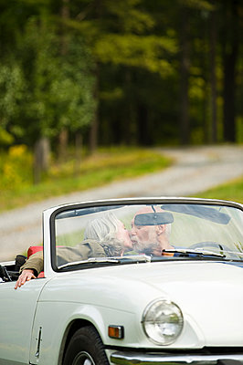 Older couple kissing in convertible on dirt road - p555m1411193 by Alberto Guglielmi