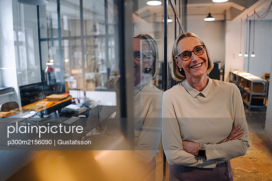 Portrait of smiling mature businesswoman leaning against glass pane in office - p300m2156090 by Gustafsson