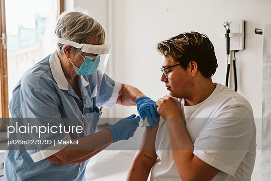 Senior female healthcare worker giving vaccine to young male patient during COVID-19 - p426m2279799 by Maskot