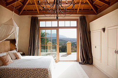 Bed with canopy and French doors leading to balcony in bedroom - p1023m756101f by Martin Barraud