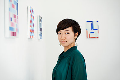 Woman with short black hair wearing green shirt standing in art gallery, looking at camera. - p1100m1531065 by Mint Images