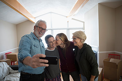 Parents helping affectionate lesbian couple move into new house, taking selfie - p1192m1560017 by Hero Images