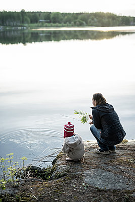Finland, Kuopio, mother and daughter crouching at a lake - p300m2030175 von Petra Silie