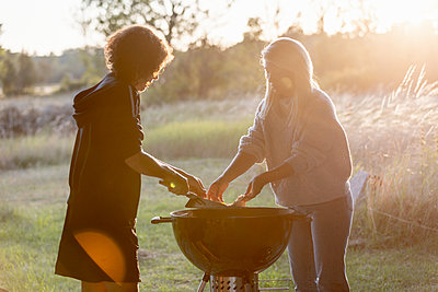Women preparing food on barbecue - p312m2262613 by Ulf Huett Nilsson