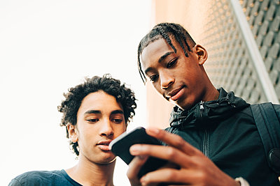 Low angle view of teenage boy showing mobile phone to friend in city - p426m2075076 by Maskot